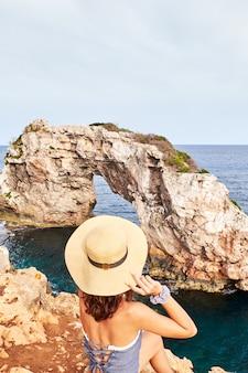 Jeune fille avec chapeau assis et regardant le rocher d'es pontas à majorque. espagne
