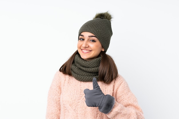 Jeune fille avec un chapeau d'hiver sur blanc isolé donnant un coup de pouce geste