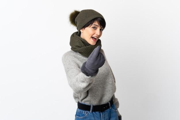 Jeune fille avec chapeau d'hiver faisant le geste de l'argent