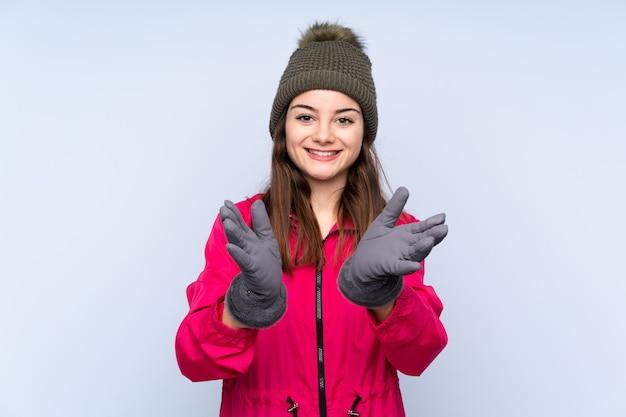 Jeune fille avec un chapeau d'hiver isolé sur bleu applaudissant après présentation lors d'une conférence