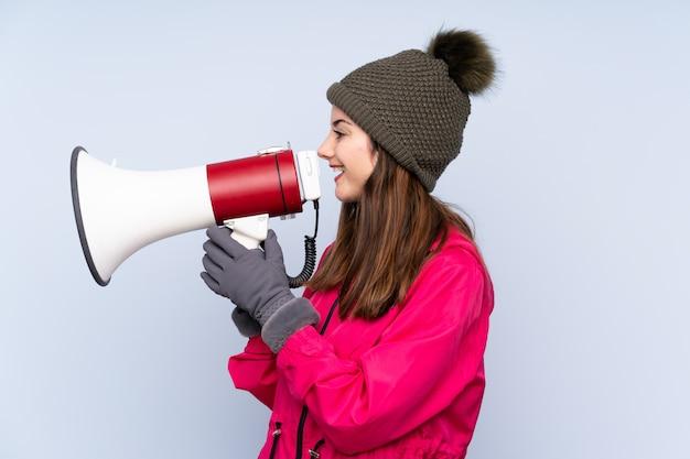 Jeune fille avec chapeau d'hiver isolé sur bleu criant à travers un mégaphone