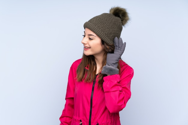 Jeune fille avec un chapeau d'hiver isolé sur le mur bleu en écoutant quelque chose en mettant la main sur l'oreille