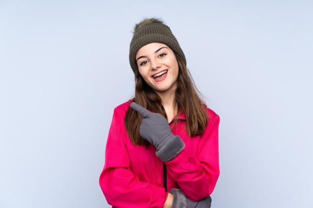 Jeune fille, à, chapeau hiver, isolé, sur, mur bleu, surpris, et, pointage, côté