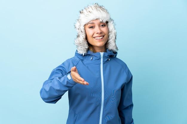 Jeune fille avec un chapeau d'hiver isolé sur une poignée de main bleue après une bonne affaire