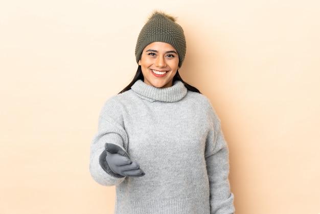 Jeune fille avec un chapeau d'hiver sur le mur beige poignée de main après une bonne affaire