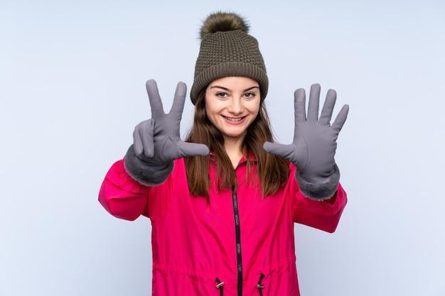Jeune fille, à, chapeau hiver, sur, mur bleu, compter, huit, à, doigts