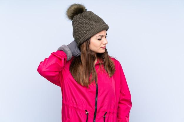 Jeune fille avec un chapeau d'hiver sur un mur bleu avec des maux de cou