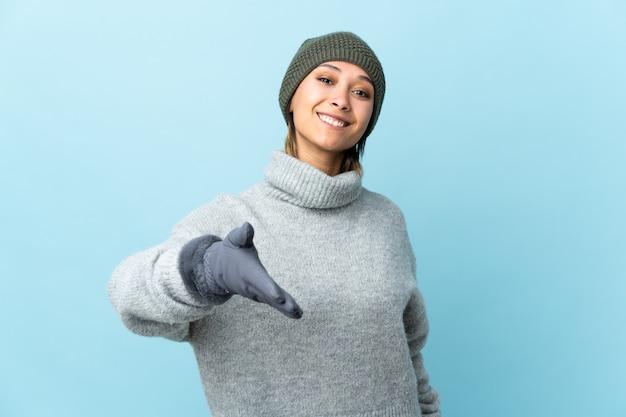 Jeune fille avec un chapeau d'hiver sur le mur bleu poignée de main après une bonne affaire