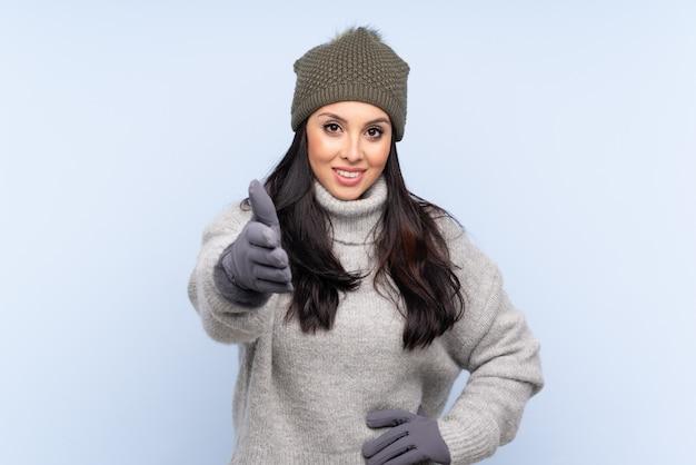 Jeune fille avec chapeau d'hiver sur le mur bleu poignée de main après une bonne affaire