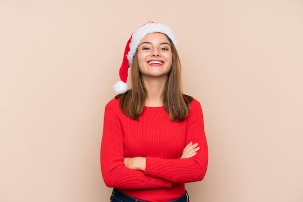 Jeune fille avec un chapeau de noël sur mur isolé en riant