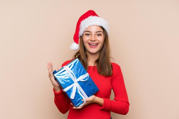 Jeune fille avec un chapeau de noël tenant un cadeau sur un mur isolé