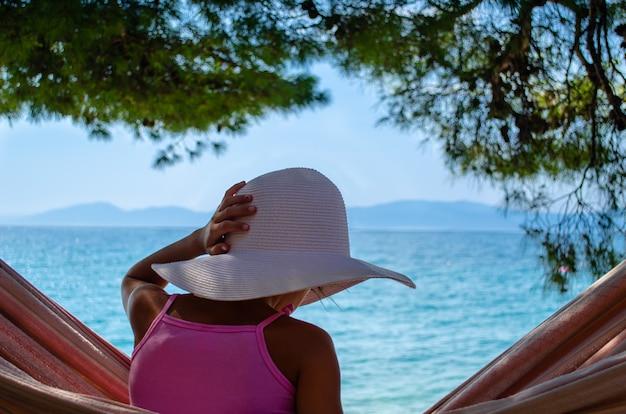 Jeune fille avec un chapeau de paille blanc assis dans un hamac sous le pin surplombant une plage