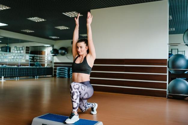 La jeune fille en chaussures de sport marche sur la plate-forme step et fait les exercices, l'aérobic en salle de sport