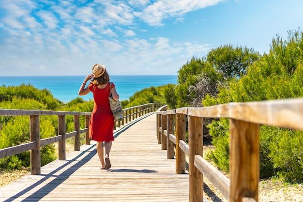 Une jeune fille sur le chemin en bois à playa moncayo à guardamar del segura à côté de torrevieja