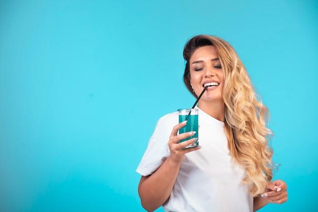 Jeune fille en chemise blanche buvant un cocktail bleu.