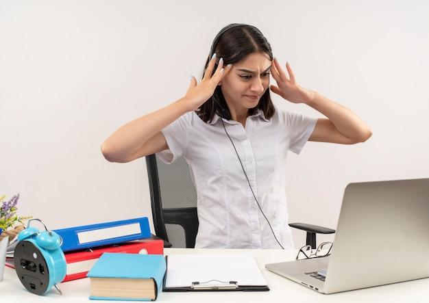 Jeune fille en chemise blanche et un casque, à la confusion tenant sa tête avec les mains assis à la table avec des dossiers et un ordinateur portable sur un mur blanc