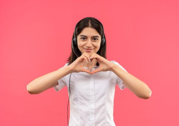 Jeune fille en chemise blanche et casque, faisant le geste du coeur avec les doigts souriant debout sur le mur rose