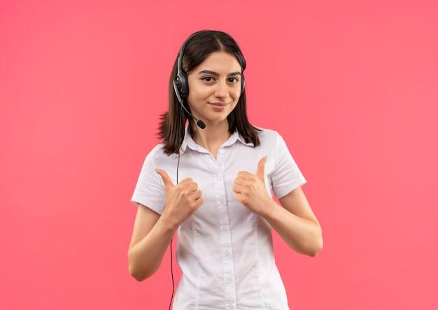 Jeune fille en chemise blanche et casque, regardant vers l'avant en souriant montrant les pouces vers le haut debout sur le mur rose