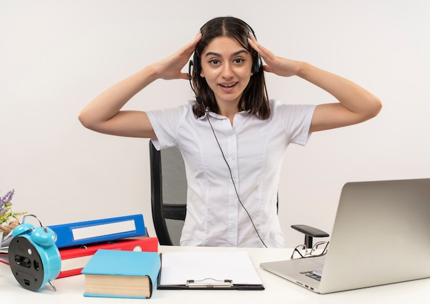 Jeune fille en chemise blanche et casque, tenant sa tête avec les mains à la confusion assis à la table avec des dossiers et un ordinateur portable sur un mur blanc