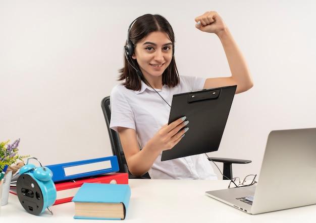 Jeune fille en chemise blanche et écouteurs, tenant le poing serrant le presse-papiers heureux et positif assis à la table avec des dossiers et un ordinateur portable sur un mur blanc