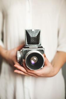 La jeune fille à la chemise blanche est titulaire d'un bel appareil photo rétro vintage. fermer.