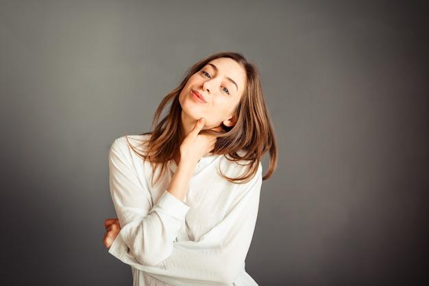 Jeune fille en chemise blanche, mains vers le haut, sur un mur gris. honnête et émotif.