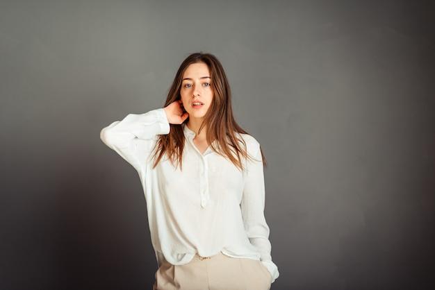 Jeune fille en chemise blanche sur un mur gris. femme française en chemisier blanc contre un mur de murs gris. sans retouche. sans maquillage.