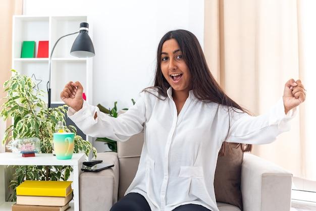 Jeune fille en chemise blanche et pantalon noir serrant les poings heureux et excité se réjouissant de son succès assis sur la chaise dans un salon lumineux