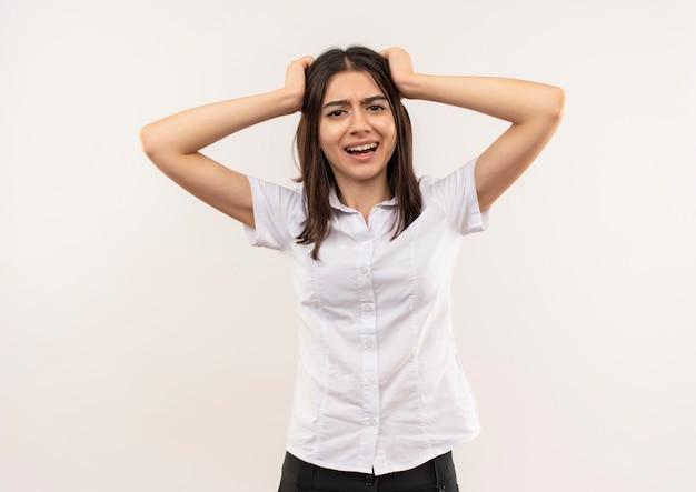 Jeune fille en chemise blanche se déchaîne en tirant ses cheveux debout sur un mur blanc