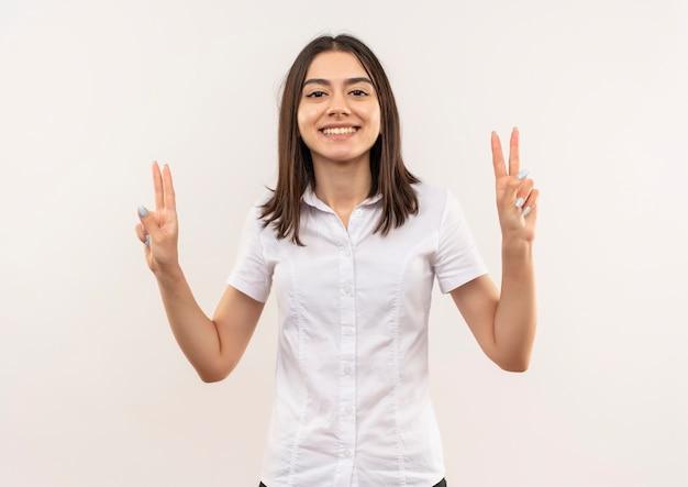 Jeune fille en chemise blanche souriant joyeusement montrant la victoire chanter avec les deux mains debout sur un mur blanc