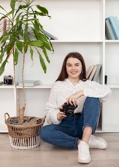 Jeune fille en chemise blanche tenant un appareil photo rétro