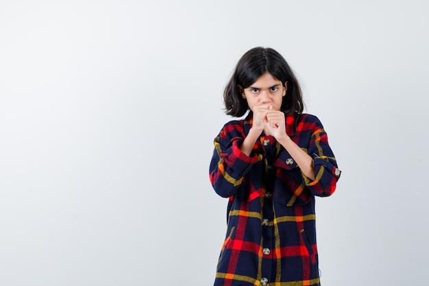Jeune fille en chemise à carreaux debout dans une pose de boxeur et semblant puissante, vue de face.