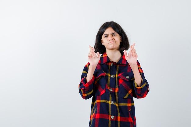 Jeune fille en chemise à carreaux en gardant les doigts croisés et l'air sérieux, vue de face.