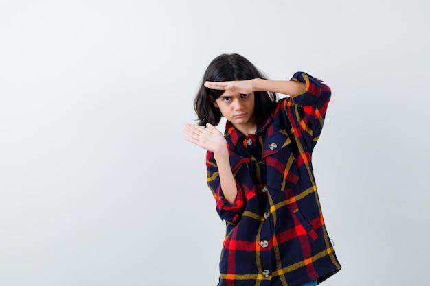 Jeune fille en chemise à carreaux montrant le geste des écailles et l'air sérieux, vue de face.