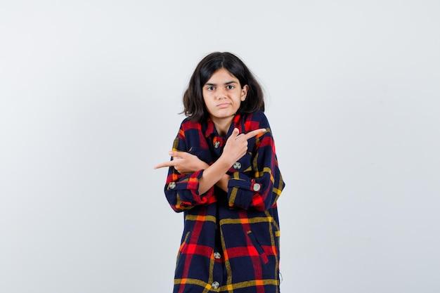 Jeune fille en chemise à carreaux pointant dans des directions opposées et à la grave , vue de face.