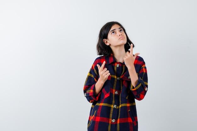 Jeune fille en chemise à carreaux pointant vers le haut avec l'index et l'air mignon, vue de face.