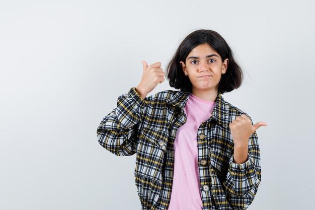 Jeune fille en chemise à carreaux et t-shirt rose montrant les pouces vers le haut avec les deux mains et ayant l'air jolie, vue de face.