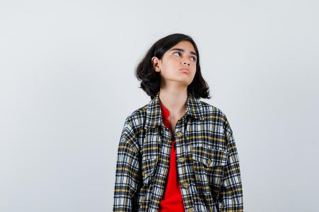 Jeune fille en chemise à carreaux et t-shirt rouge en détournant les yeux tout en se présentant à la caméra et en ayant l'air sérieux, vue de face.