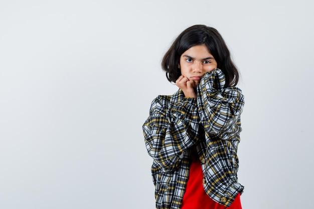 Jeune fille en chemise à carreaux et t-shirt rouge, les joues appuyées sur les paumes et l'air sérieux, vue de face.