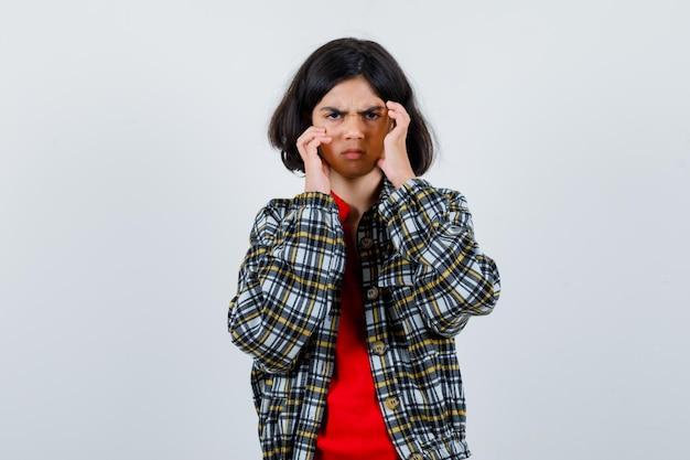 Jeune fille en chemise à carreaux et t-shirt rouge mettant les mains face à face et regardant en colère, vue de face.
