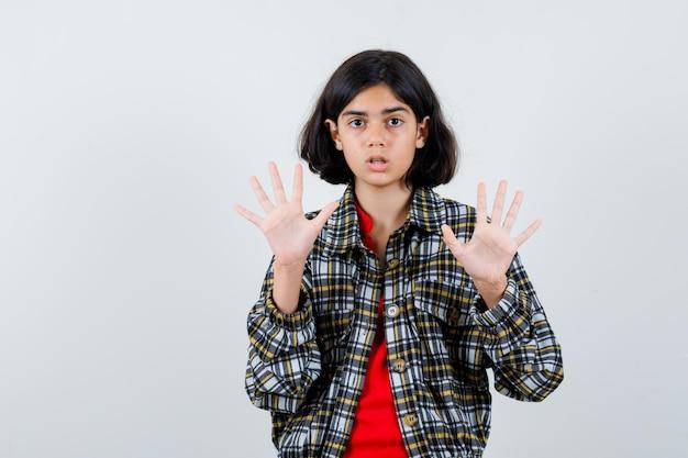 Jeune fille en chemise à carreaux et t-shirt rouge montrant des panneaux d'arrêt et l'air surpris, vue de face.