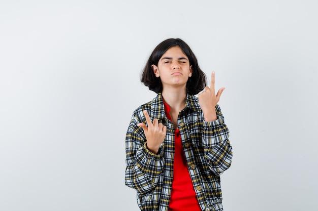 Jeune fille en chemise à carreaux et t-shirt rouge pointant vers le haut et semblant mignonne, vue de face.