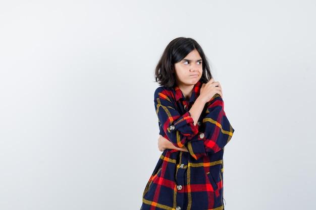 Jeune fille en chemise à carreaux tenant la main sur l'épaule, regardant loin et l'air mignon, vue de face.