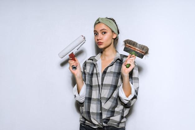 Jeune fille en chemise à carreaux tenant un pinceau et un rouleau pour peindre les murs