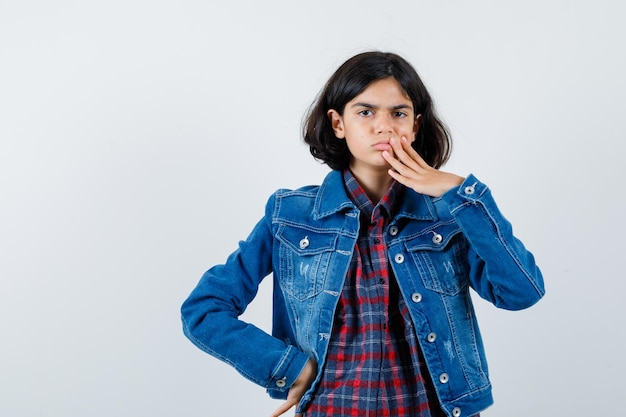 Jeune fille en chemise à carreaux et veste en jean couvrant la bouche avec la main tout en tenant la main sur la taille et l'air pensif, vue de face.