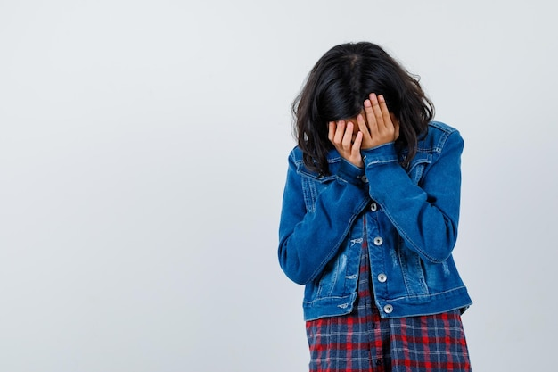 Jeune fille en chemise à carreaux et veste en jean couvrant le visage avec les mains et l'air harcelé, vue de face.
