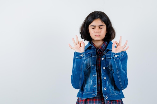 Jeune fille en chemise à carreaux et veste en jean méditant et ayant l'air calme, vue de face.