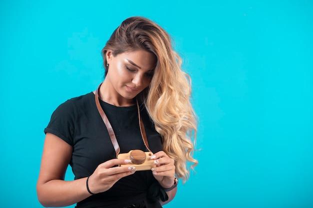 Une jeune fille en chemise noire a pendu un appareil photo jouet à son cou et le regarde.