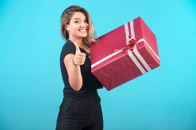 Jeune fille en chemise noire tenant une grande boîte-cadeau et fait le pouce vers le haut.