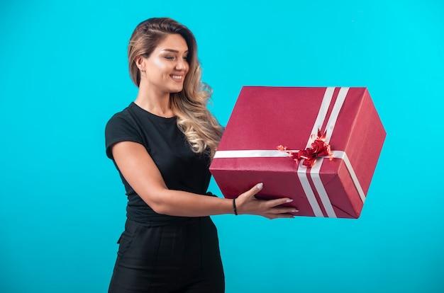 Jeune fille en chemise noire tenant une grande boîte-cadeau et se sent positif.